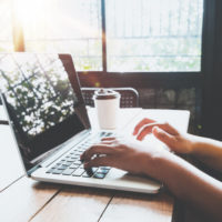 vista-lateral-de-encantadora-chica-joven-hipster-manos-trabajando-en-su-portatil-sentado-en-la-mesa-de-madera-en-una-cafeteria-mujer-que-usa-las-computadoras-en-un-cafe-estilo-del-color-de-la-v